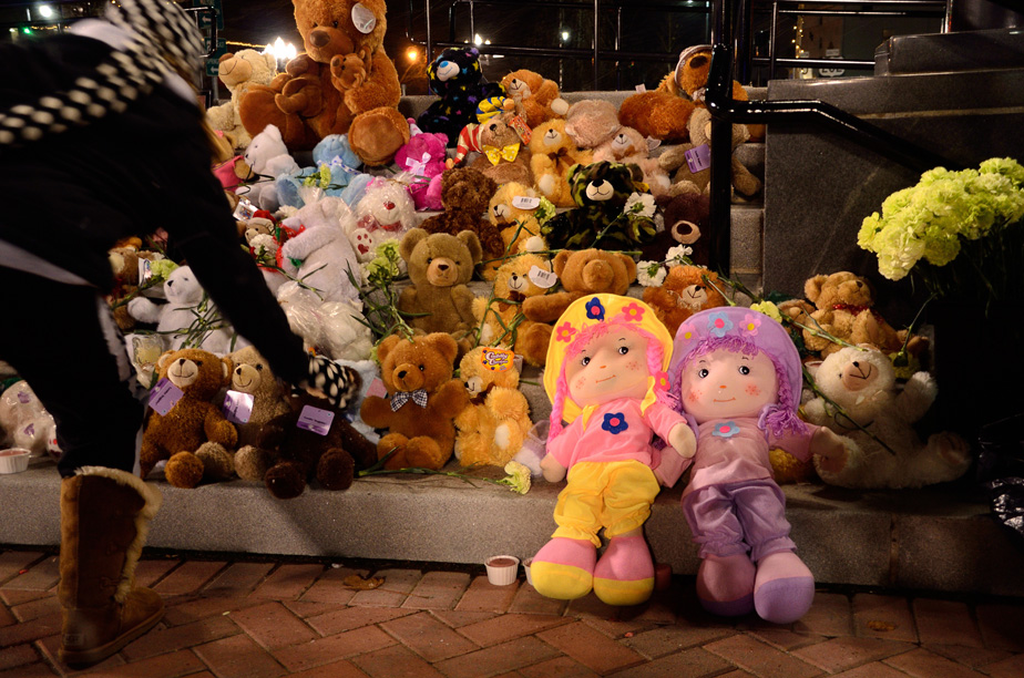 A young woman places a stuffed bear at a memorial.