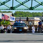 Flag bearing honor guard crossing a bridge.