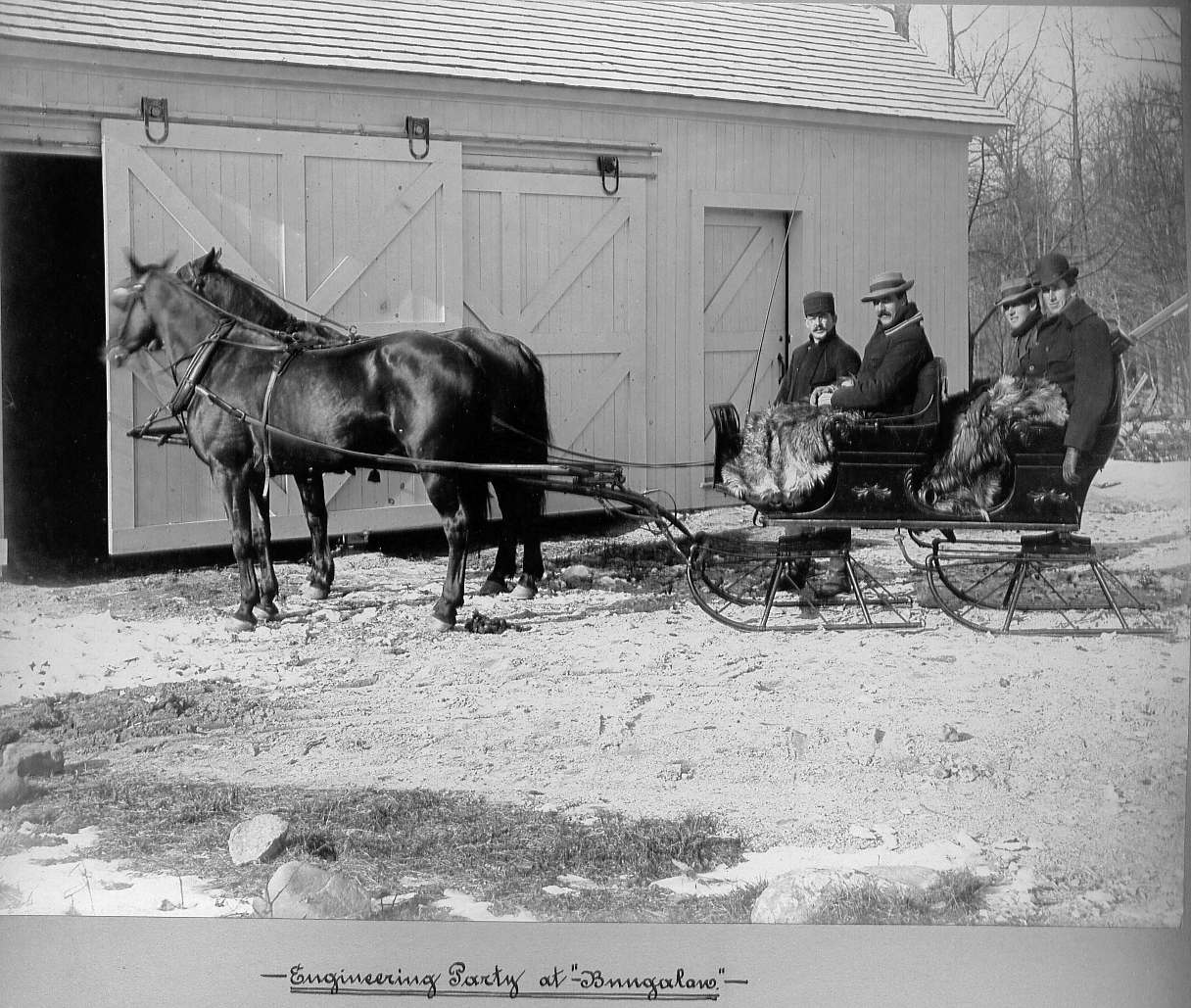 Men in horse drawn sleigh at barn