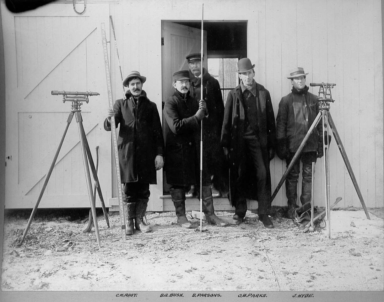Men standing with transits and surveying poles